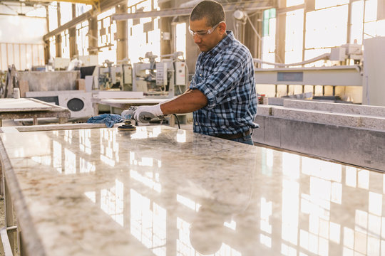 Hispanic Man Polishing Stone Working in Industrial Facility