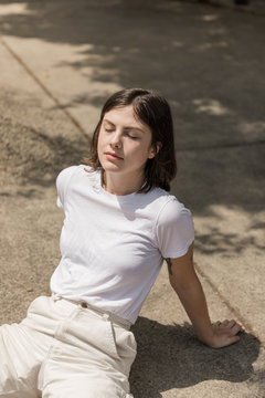 young woman sitting in driveway in the sun