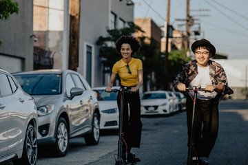 Friends riding electric scooters in the city