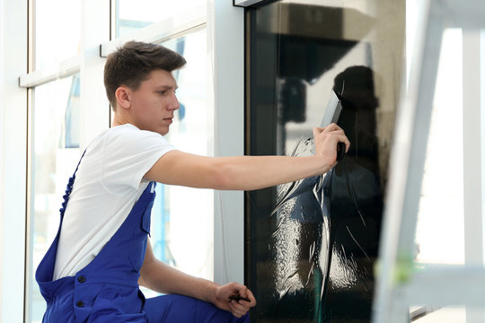 Young worker tinting window with foil indoors