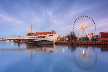 Gdansk with beautiful ferris wheel over Motlawa river at sunset, Poland.