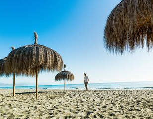 Man walking on the beach sand between umbrellas in Alamos Beach,