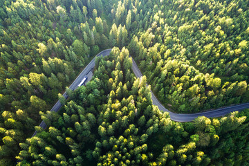 Fotobehang Pistache Aerial view of winding road in high mountain pass trough dense green pine woods.