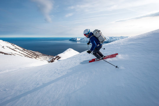 A man skiing downhill with ocean in the background in Iceland