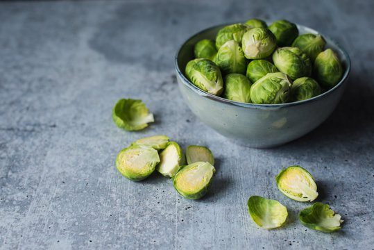 Close up image of a bowl of Brussels sprouts on a cement counter.