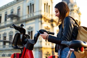 Keuken foto achterwand Historisch mon. Woman taking a rental electric bike with her cell phone.