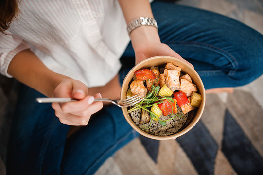 Girl holds a paper plate with healthy food sitting on the floor. Home delivery food. Healthy eating concept.