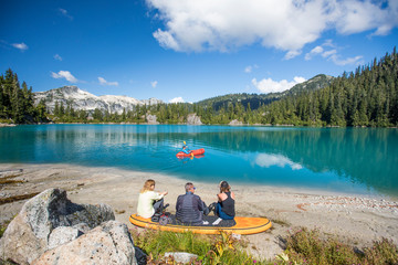 Family relaxing together at remote lake, brother paddling on lake.