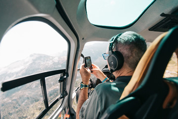 Retired man takes photo with phone from inside helicopter.