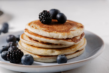 Stack of pancakes with berries on top on a white surface