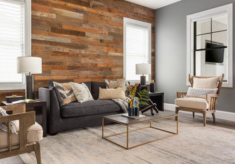 Beautiful living room in new luxury home with rustic accent wall.