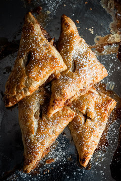 apple cinnamon baked turnovers on stainless steal pan with sugar