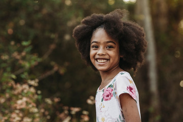 Close up portrait of young school-aged confident girl smiling at