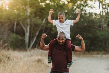 Close up portrait of school-aged son sitting on father's shoulders