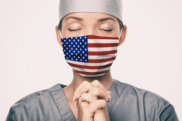 Coronavirus pandemic in the United States of America. USA american flag print on doctor's mask praying with claspeds hands in hope for help. Crying for help, disaster aid needed in the US. Fotomurales
