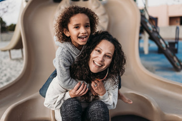 Son embracing mother on slide outside at park playground at dusk