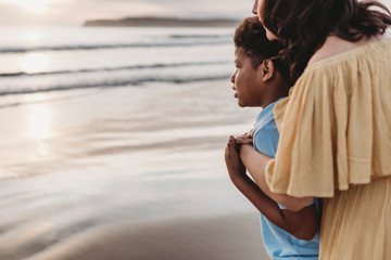 Side view of young mom embracing son at seashore during sunset