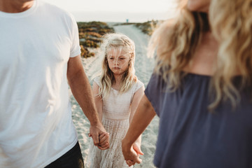 Serious girl making sad face walking with parents at beach