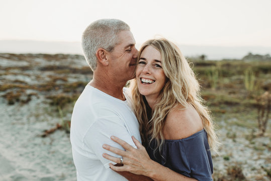 Married couple embracing at beach during sunset