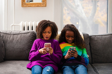Sisters in sweaters using mobile phones while sitting on sofa at home