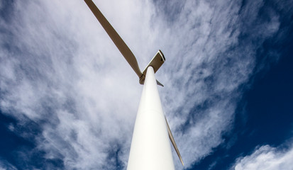 Wind Turbine low angle against cloudy blue sky