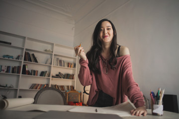 smiling asian woman  in a creative studio