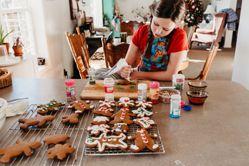Girl Decorating Christmas Cookies with Icing and Sprinkles