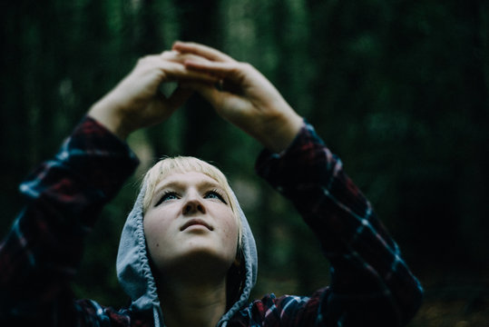 Young woman looking up in dark forest while taking a picture