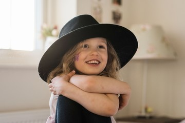 portrait of a young girl smiling at home playing dress up