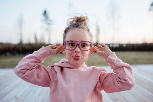 portrait of a young girl pulling silly faces with pink sparkly glasses