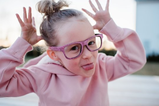 portrait of a young girl pulling silly faces with sparkly glasses on
