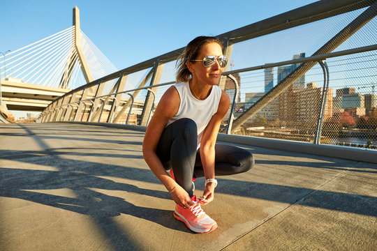 An athletic woman ties her shoe in front of the Zakim Bridge in Boston