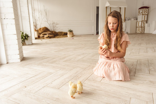 girl playing with ducks for Easter