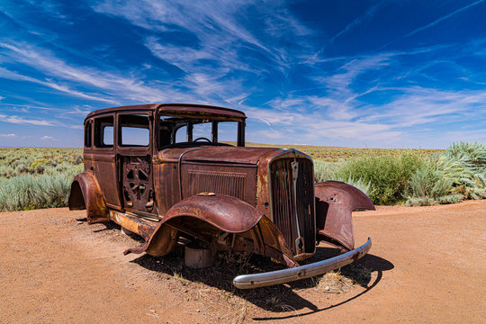 An antique rusted car in the Petrified Forest National Park marks the path of Route 66.