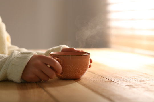 Woman with cup of tasty coffee at wooden table, closeup. Good morning