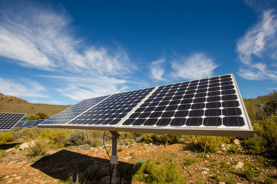 Close up wide angle view of photovoltaic solar panels on an off the grid electricity instalation on a farm in the Karoo outside Touwsrivier in the western cape of south africa