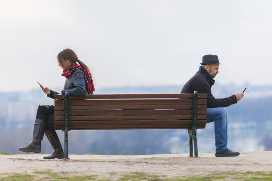 man and woman sitting apart on a bench