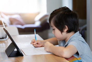 School kid self isolation using tablet for his homework, Child doing homework by using digital...