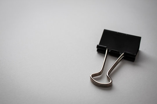 black binder clip paper clip on white paper background in the top right corner with empty negative space