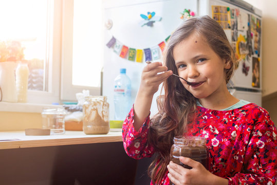 Cute happy young smiling girl eat homemade sweet chocolate paste spread from big glass jar with joy and pleasure