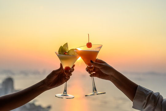 Couple enjoying of Cheers glass of cocktail in a restaurant  at sunset view sea. Cocktail, Couple, Honeymoon, Dinner, Wine, Romantic concept.