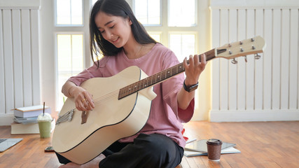 Cropped shot of a Teenage girl playing a guitar while staying at home while quarantine the Covid-19 virus.