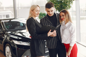People in a car salon. Couple buying the car. Elegant women with handsome man. Manager helps people.