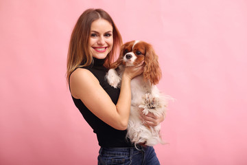 Beautiful girl in a studio. Stylish woman on a pink background. Lady with a dog