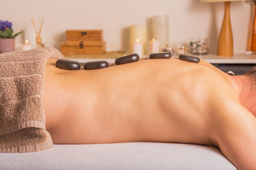 "Man with stones on massage table at spa with body treatment. Person lying and relaxing during ""hot stone massage""."