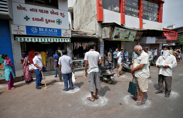People queue standing in circles drawn with chalk to maintain safe distance as they wait to buy medicine during a 21-day nationwide lockdown to limit the spreading of coronavirus disease (COVID-19), in Ahmedabad