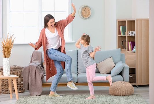 Happy mother and her little daughter dancing at home