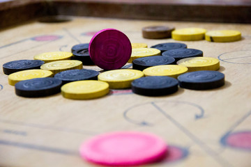 A game of carom set and ready to play. A game of carrom with pieces carrom man on the board carrom. Carom board game, selective focus.