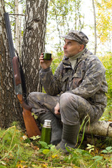 a hunter drinks tea while resting on a fallen tree