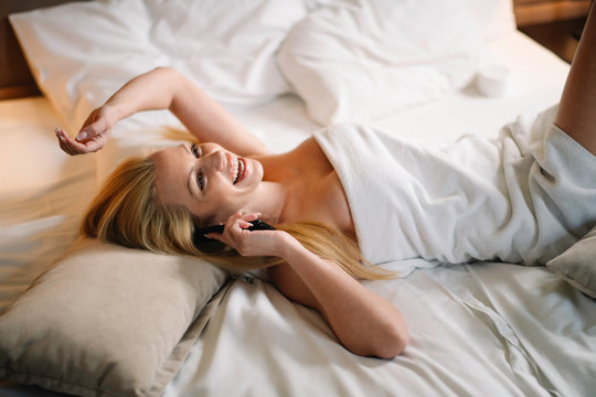 Beautiful woman enjoying in hotel room. Young happy woman talking on the phone.